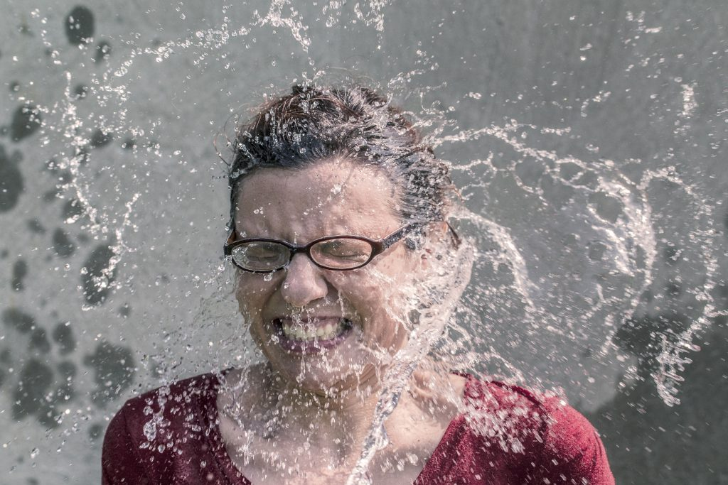 woman wearing glasses being splashed in the face with water