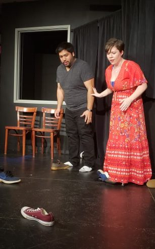 Two actors on a stage looking with surprise at two shoes sitting on the stage